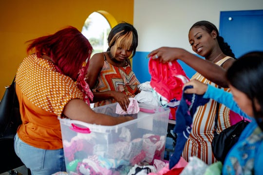 From left, Mary D. Theodore, Barbara Colin, and Marie O. Jean browse through a bin of donated baby clothing at the Immokalee Community Baby Shower at the Boys & Girls Club in Immokalee on Thursday, May 9, 2019.