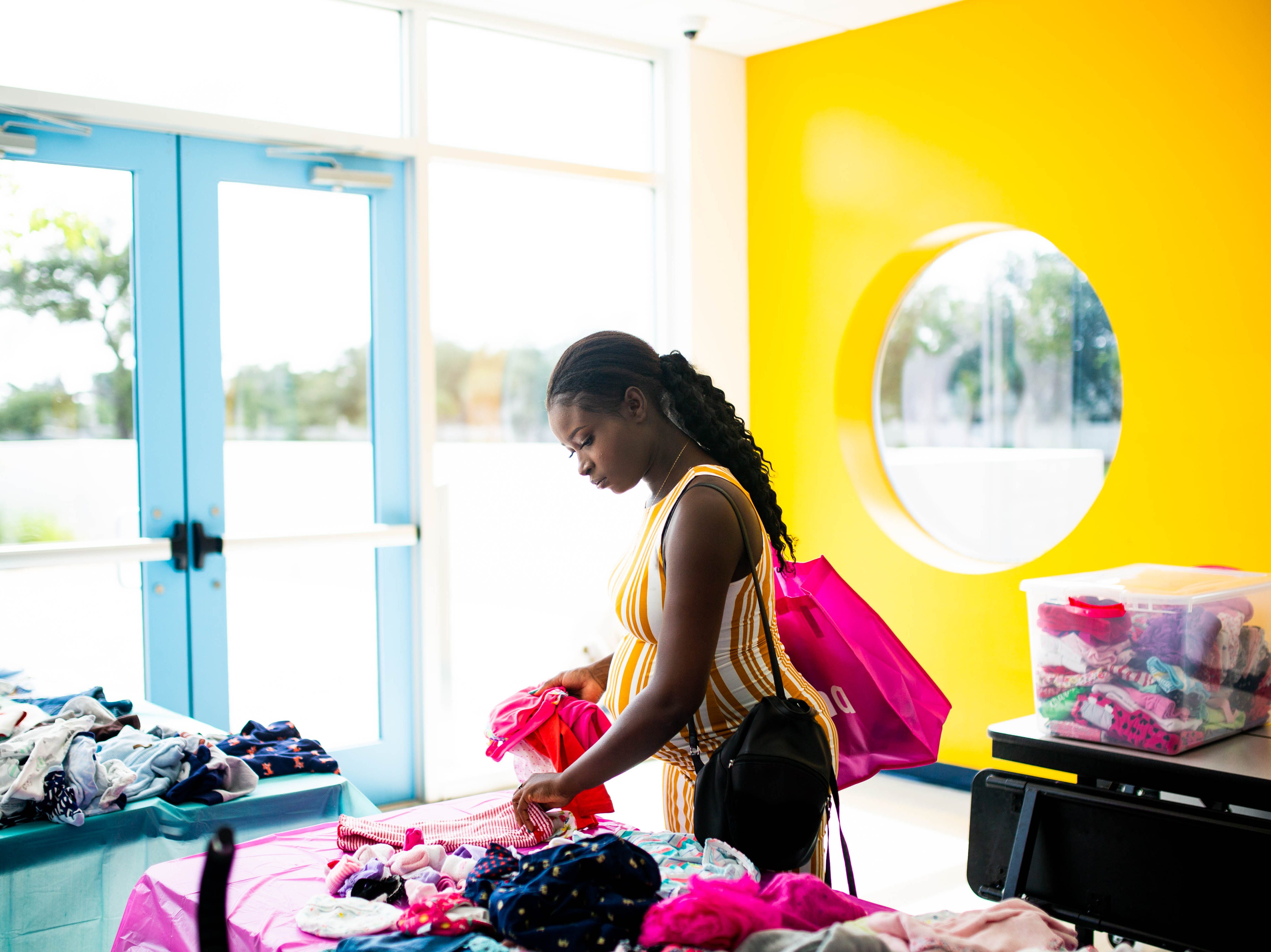 Marie O. Jean browses through a bin of donated baby clothing at the Immokalee Community Baby Shower at the Boys & Girls Club in Immokalee on Thursday, May 9, 2019. Theodore, an employee of the Boys & Girls Club, is due in July.