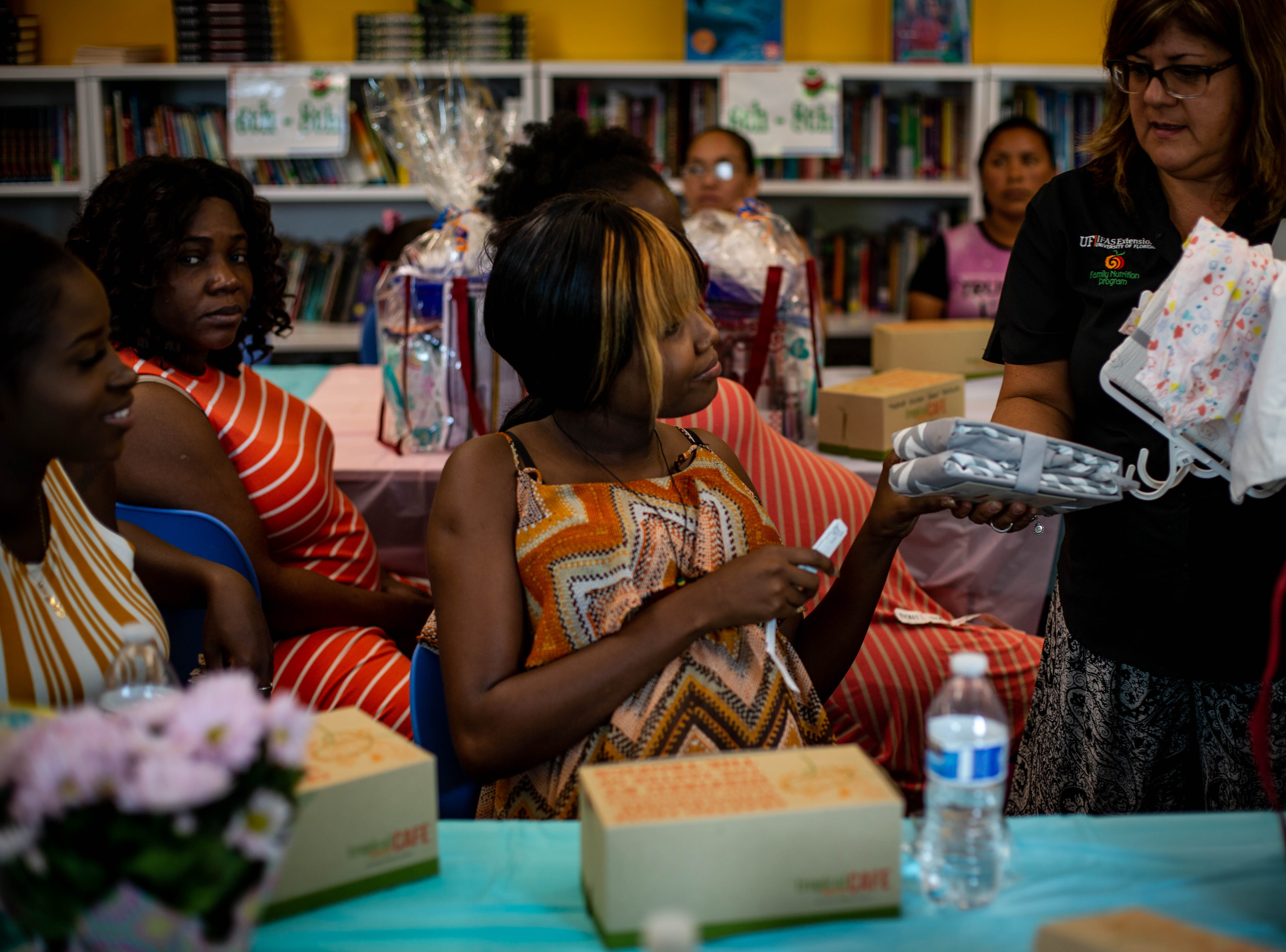Barbara Colin receives a raffle item at the Immokalee Community Baby Shower at the Boys & Girls Club in Immokalee on Thursday, May 9, 2019.