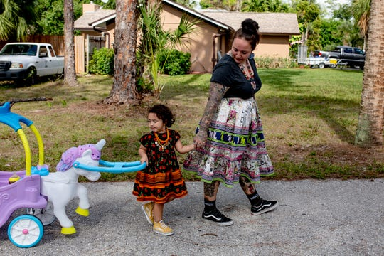 "Dakota Osceola and her daughter, Mia, walk down the driveway of their home in Naples on May 3, 2019. Many members of their family, including Dakota's mother, brother, and grandparents, live on the same street as Dakota and Mia. ""We have everything we need, and that's each other,"" she said. ""We're trying to be financially independent, trying our best to work as hard as we can to accomplish our goals, and that's really what it's been about since the beginning of the Osceolas."""