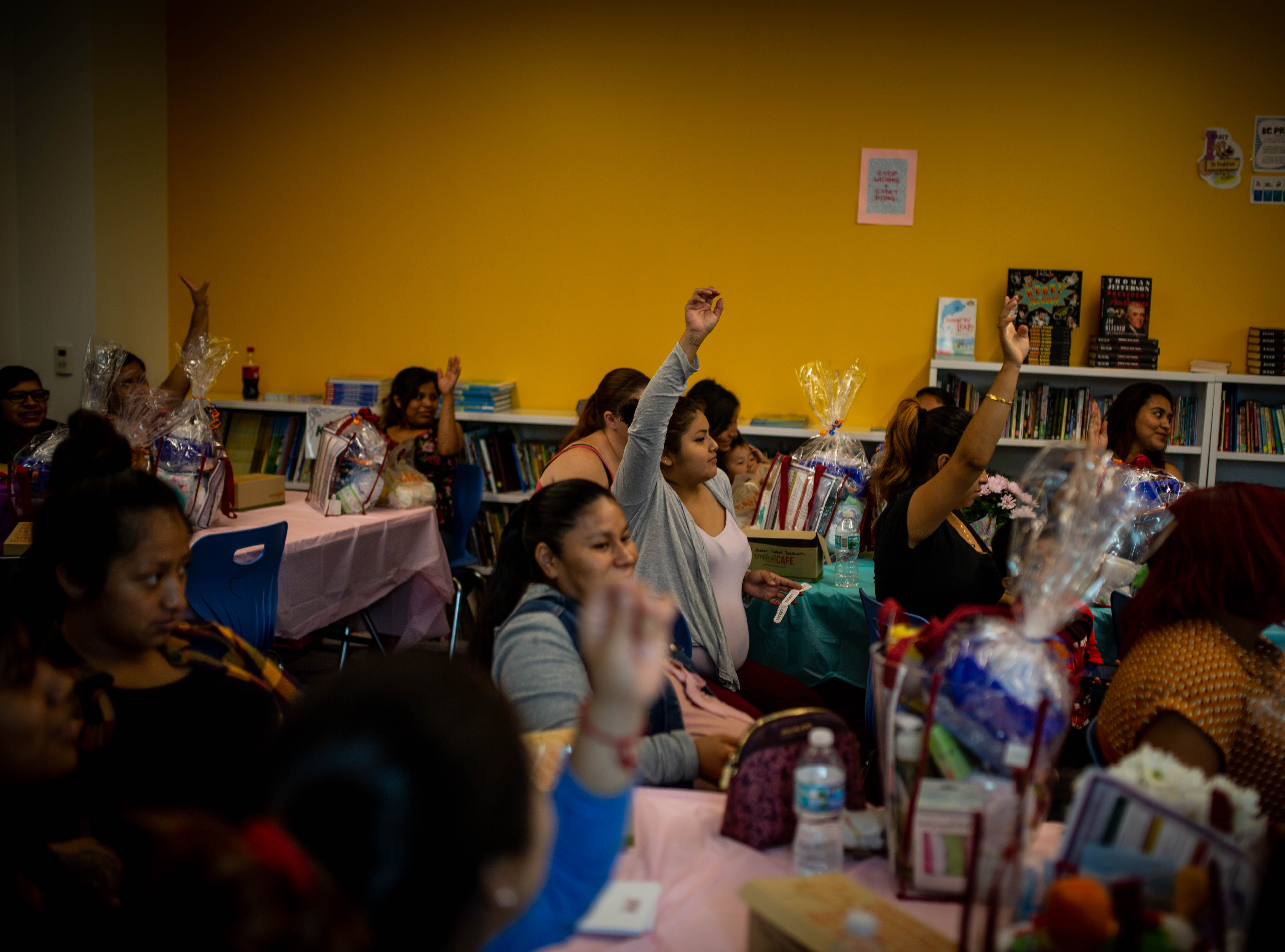 Participants raise their hands during a presentation at the fourth annual Immokalee Community Baby Shower at the Boys & Girls Club in Immokalee on Thursday, May 9, 2019.