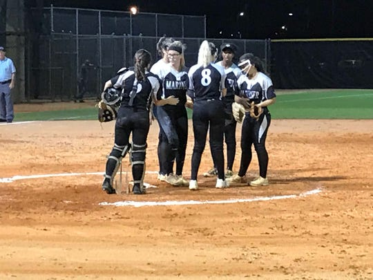 Mariner holds a conference at the mound late in Wednesday's 2-1 win over Immokalee in the Class 6A regional softball quarterfinals. Tritons pitcher Hannah Holloway tossed a six-hitter, striking out 15 and walking none.