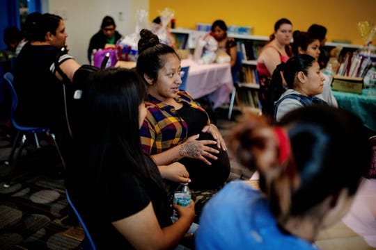 Maria Ramirez, center, and Celi Tema and listen to presentations at the Immokalee Community Baby Shower at the Boys & Girls Club in Immokalee on Thursday, May 9, 2019. During the event, many speakers presented information regarded prenatal and postnatal care.