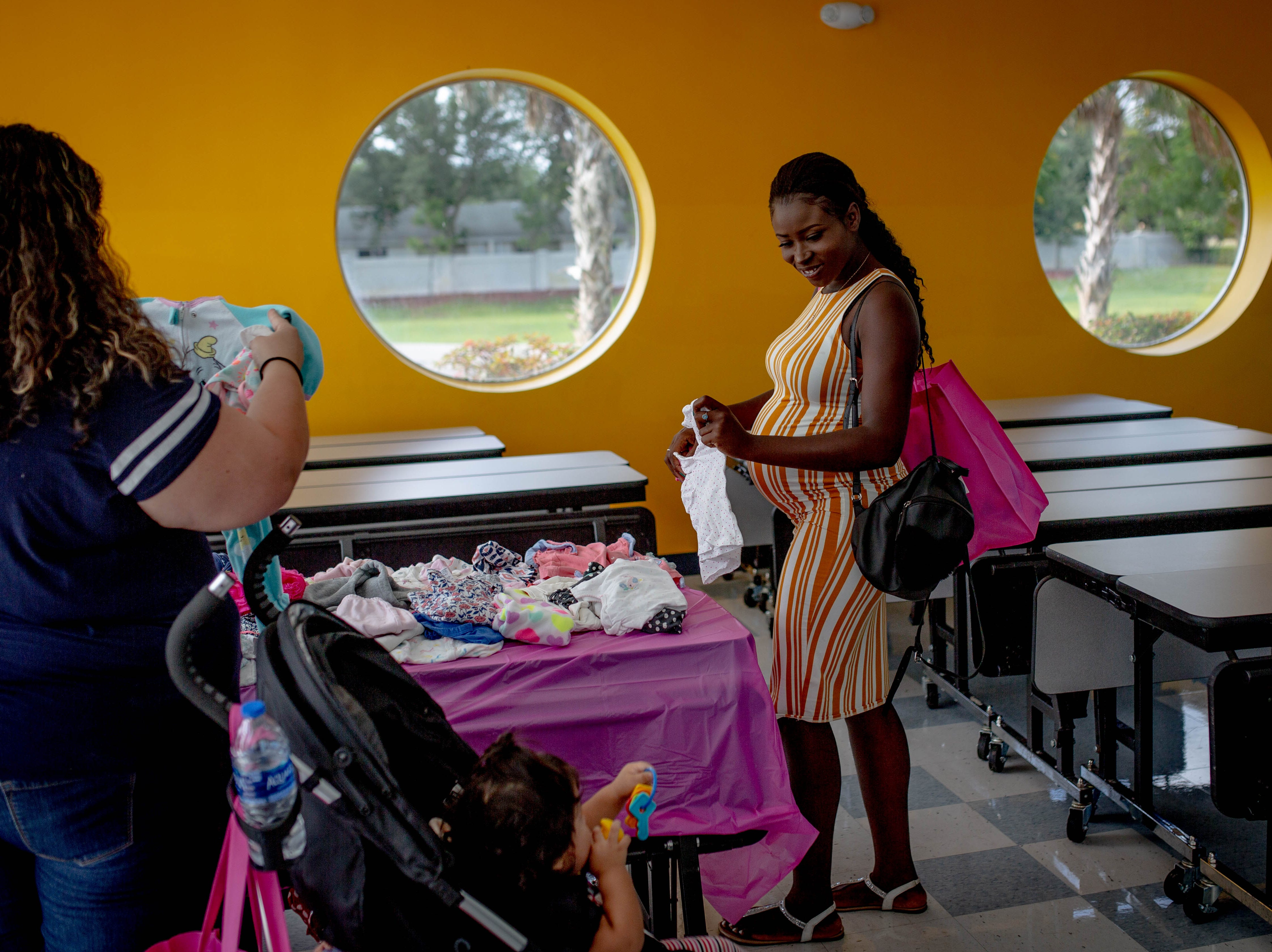 Marie O. Jean browses donated baby clothing at the Immokalee Community Baby Shower at the Boys & Girls Club in Immokalee on Thursday, May 9, 2019. Theodore, an employee of the Boys & Girls Club, is due in July.