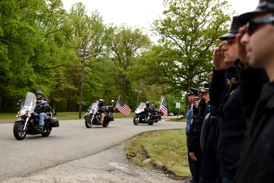 Members of the Paterson fire department salute The procession escorting The Moving Wall as it enters Garret Mountain Reservation in Woodland Park on Thursday, May 9, 2019. The wall is a  traveling half-size replica of the Vietnam Veterans Memorial.