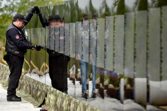 The Moving Wall, the traveling half-size replica of the Vietnam Veterans Memorial, is set up in Garret Mountain Reservation in Woodland Park on Thursday, May 9, 2019. U.S Air Force Vietnam veteran Luis Vega holds panels in place while they are secured. Vega is a member of American Legion Post 174 in Wayne.