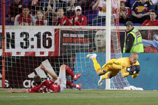 Montreal Impact goalkeeper Evan Bush, right, dives after collecting the ball, next to New York Red Bulls forward Tom Barlow during the first half of an MLS soccer match Wednesday, May 8, 2019, in Harrison.