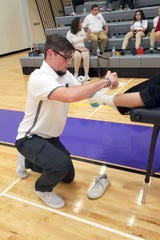 Junior Wildcat student trainer Tyler Wycoff works on his wrapping and tape skills during the New Mexico Athletic Training Challenge.