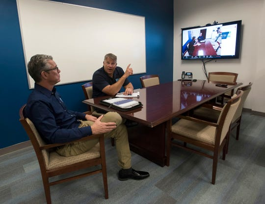 EBI Management Group CEO Mark Kilcawley and President Travis Goins prepare Wednesday for a teleconference with a client from their office at the Pensacola Co: Lab in downtown.