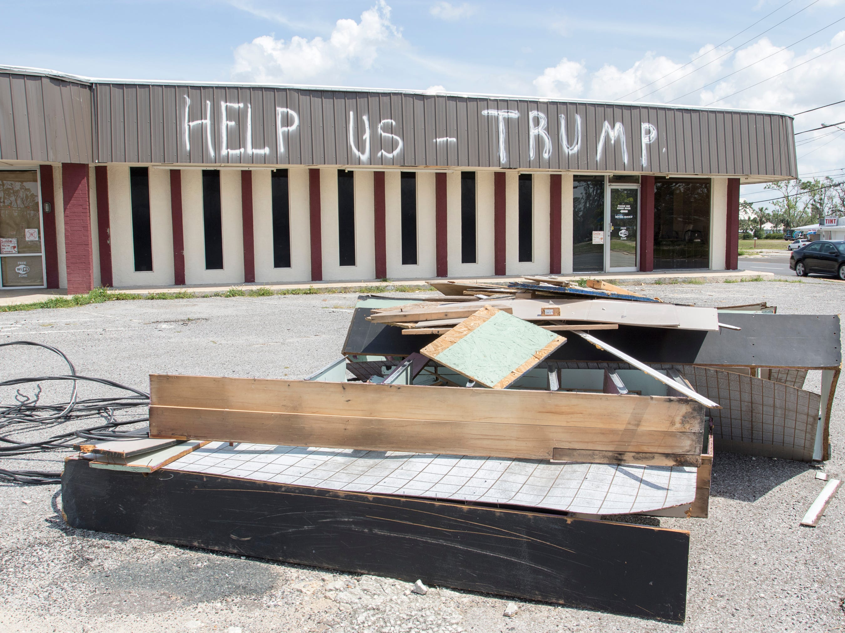 """""""Help Us - Trump"""" is still painted on a building in the Panama City, Florida on Wednesday, May 8, 2019.  Business owners Jamie and Jennifer Burton explained that they wrote this message prior to President Trump's intial visit to the area following Hurricane Michael."""