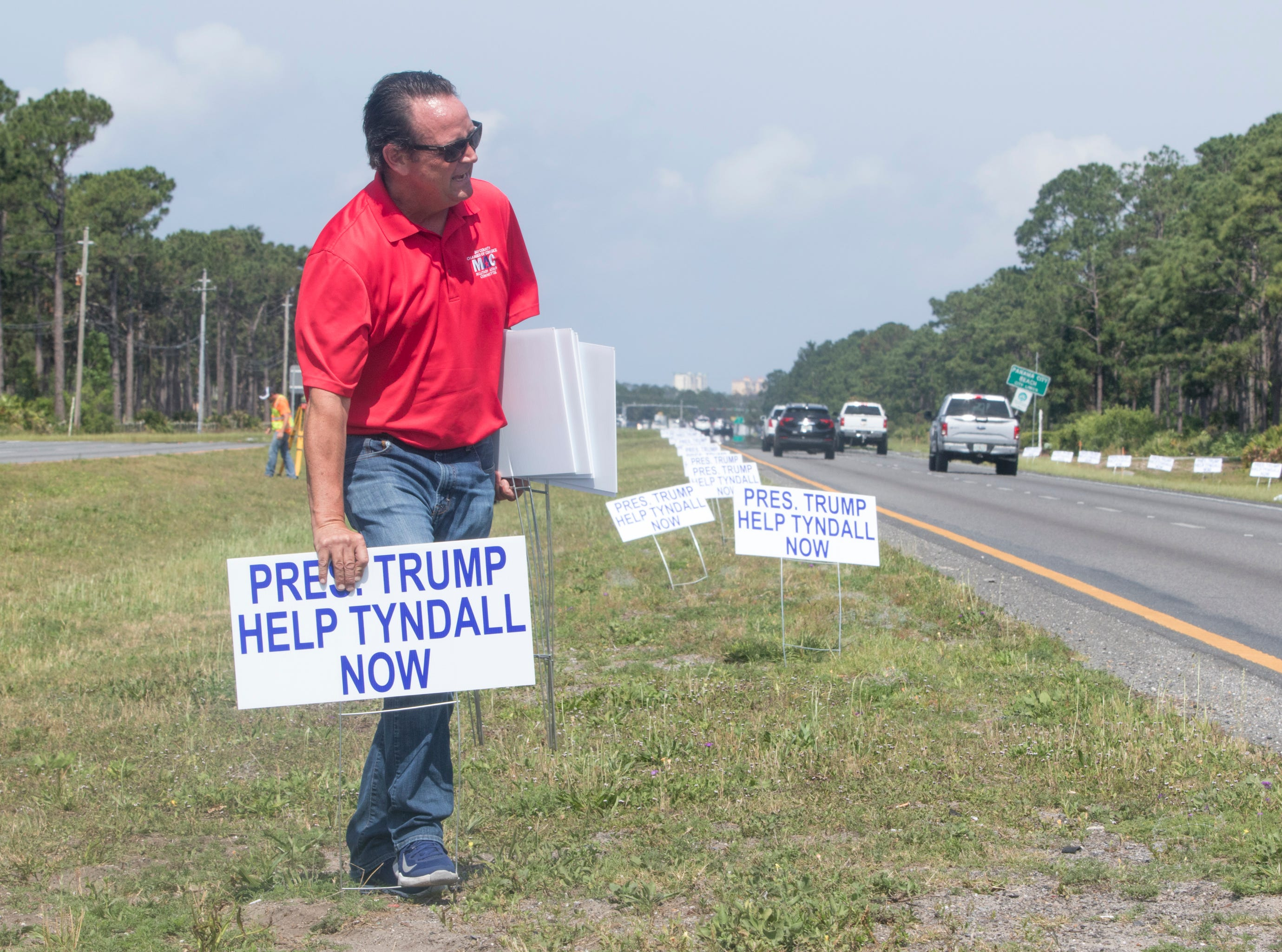 """Bret Henderson places """"Help Tyndall Now"""" signs along the roadway ahead of President Trumps visit in the Panama City Beach, Florida on Wednesday, May 8, 2019."""