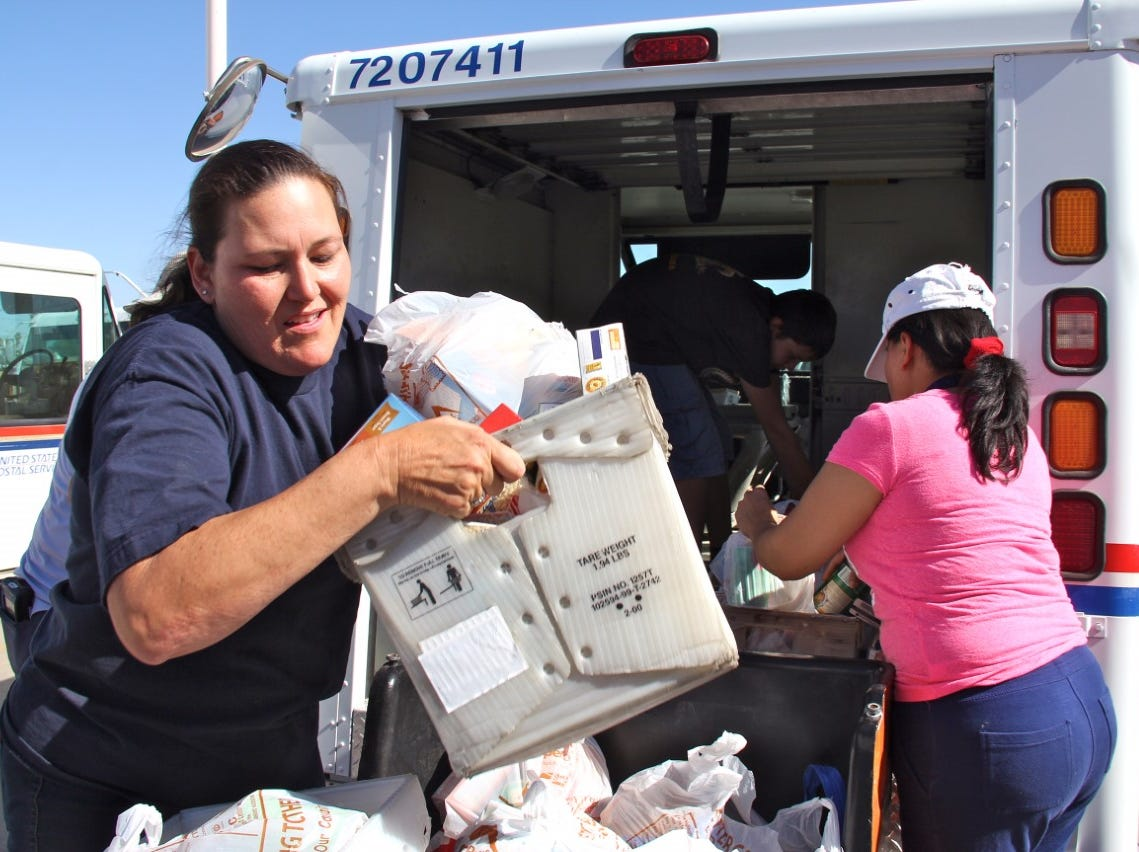 """Volunteers unload boxes of food collected during the 2018 """"Stamp out Hunger"""" Food Drive."""