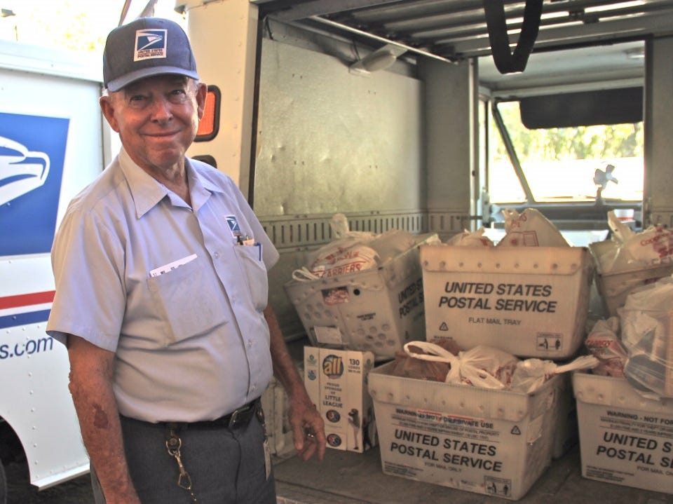 """A letter carrier stands by his truck with boxes full of food collected for the 2018 """"Stamp out Hunger"""" Food Drive."""