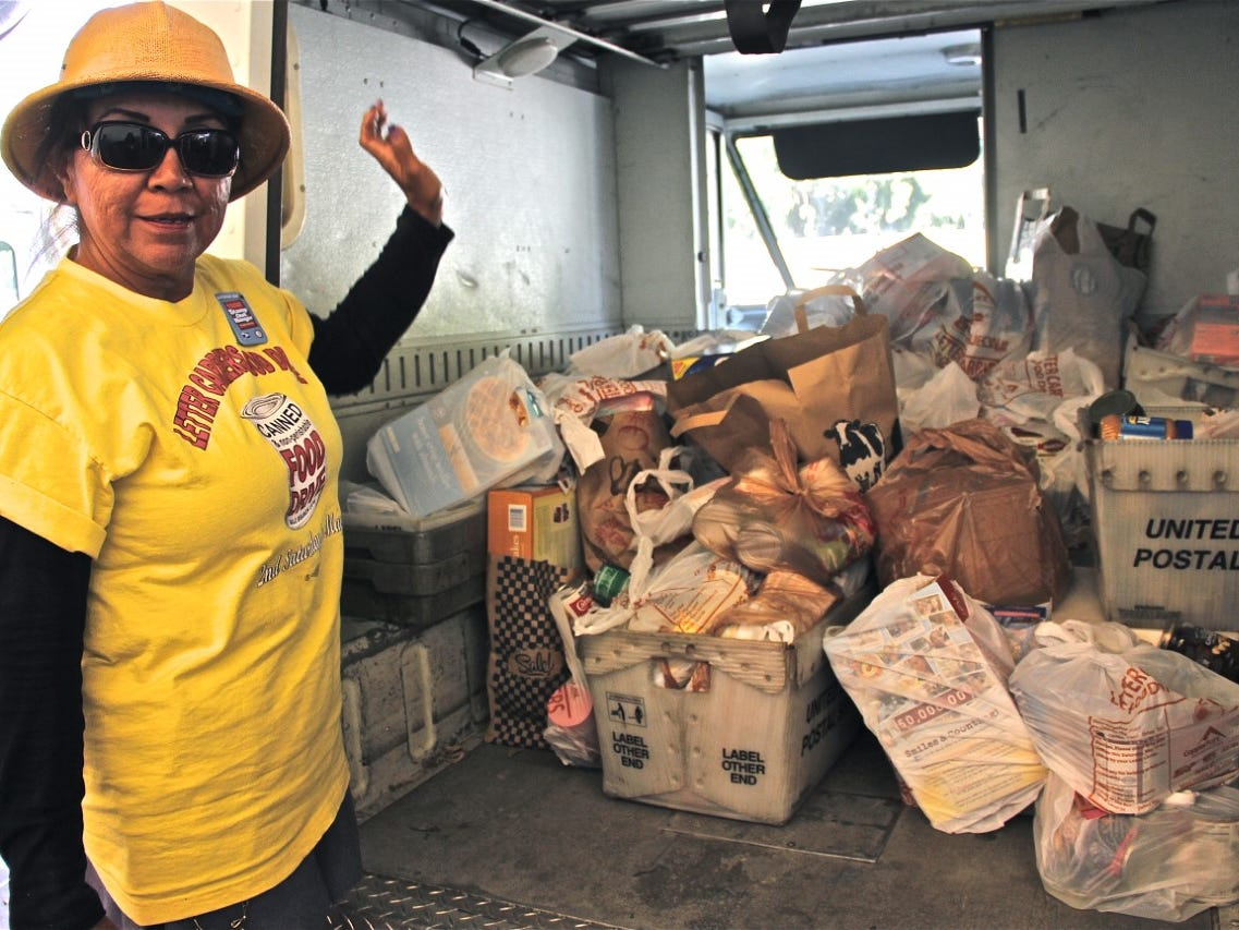 """A letter carrier stands next to truck with food collected through the 2018 """"Stamp Out Hunger"""" Food Drive."""