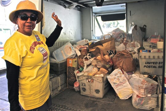 "A letter carrier stands next to truck with food collected through the 2018 ""Stamp Out Hunger"" Food Drive."