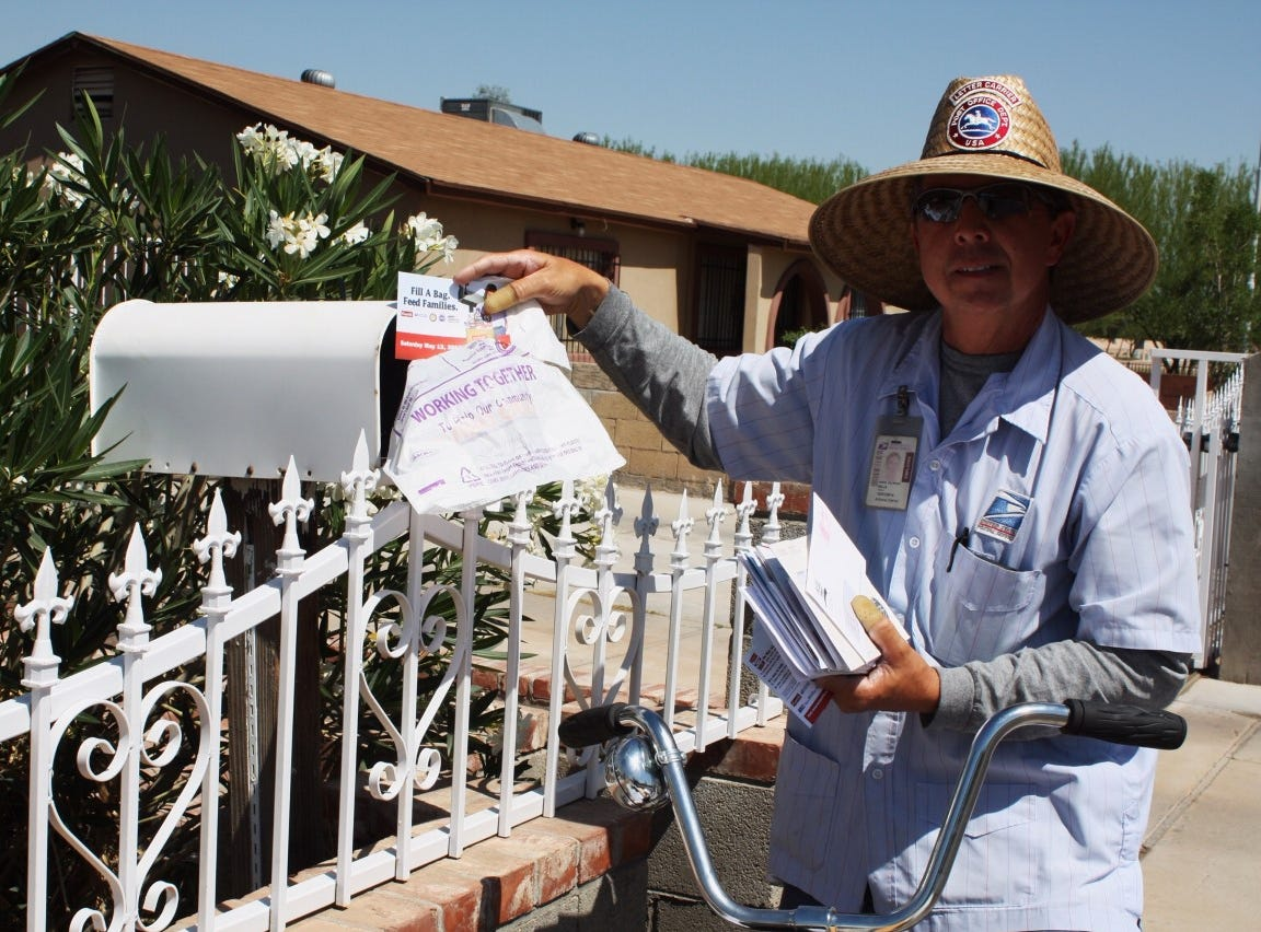"""A letter carrier distributes reminders for the 2018 """"Stamp Out Hunger"""" Food Drive."""