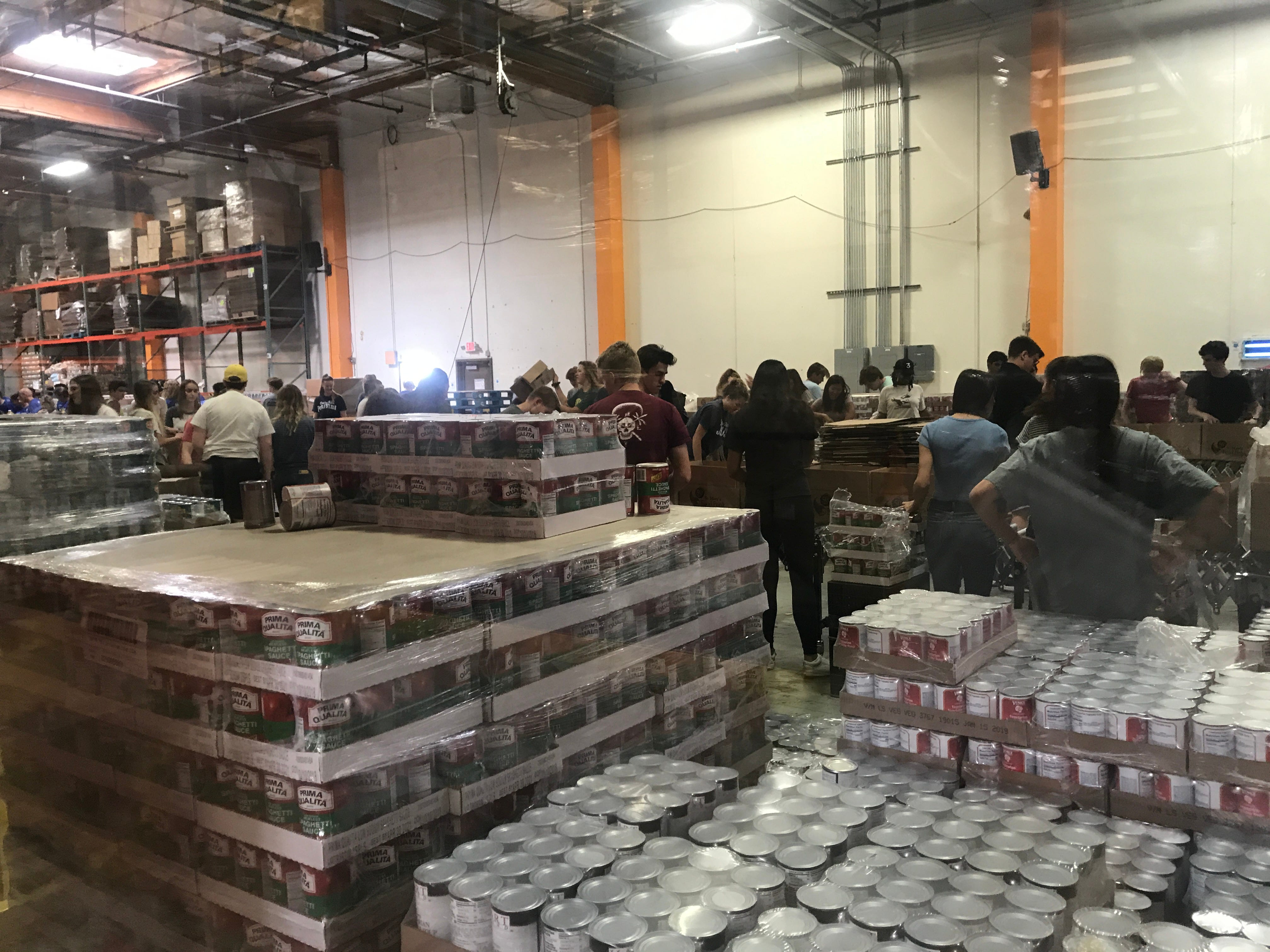 Volunteers at St. Mary's Food Bank pull cans from pallets to stock emergency food boxes on May 9, 2019.