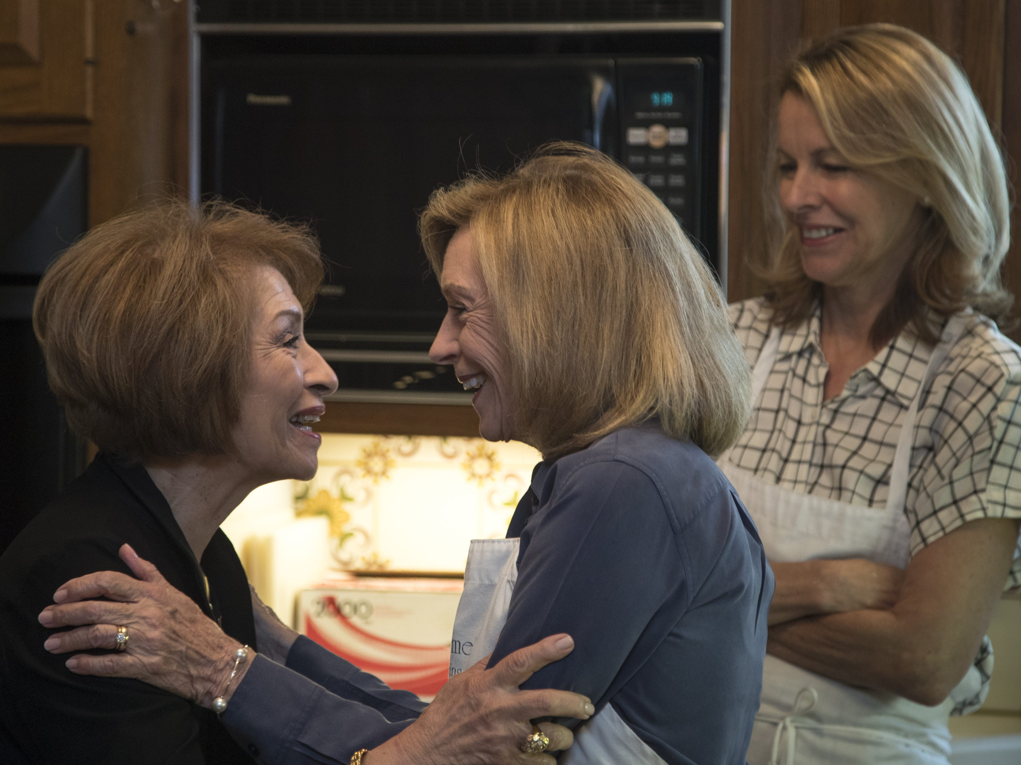 Barbara Fenzl (center) greets Nohra Kellough (left) as she arrives for a cooking class, May 7, 2019, at Les Gourmettes Cooking School, 6610 N. Central Ave., Phoenix. Looking on is Barbara's assistant, Kim Howard (right).