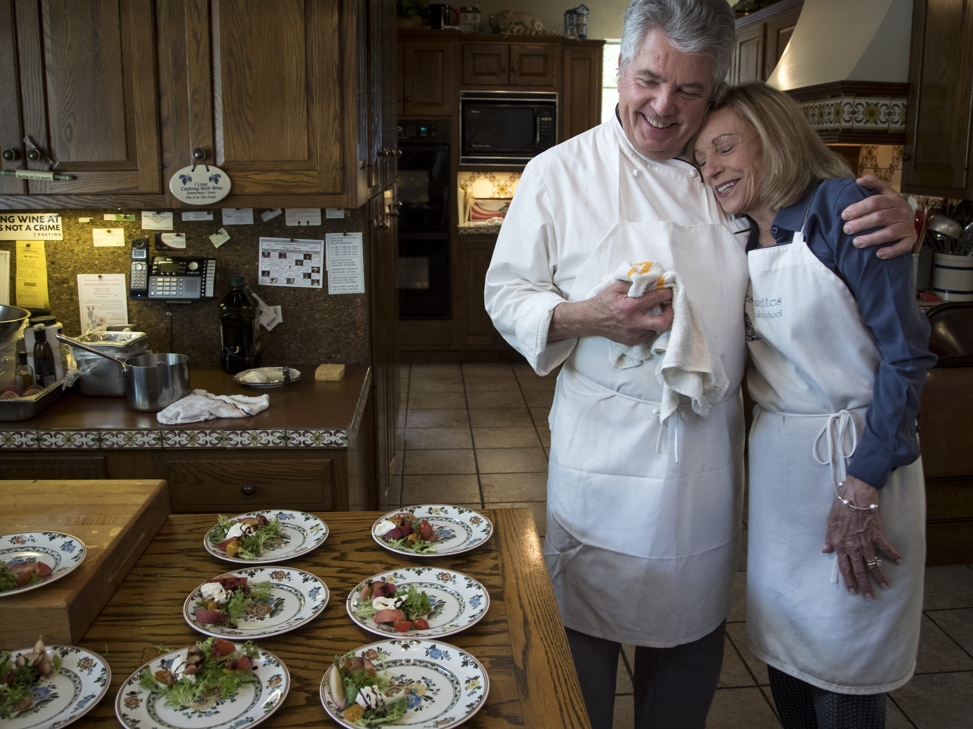 Barbara Fenzl (right) gets a hug from chef Vincent Guerithault toward the end of one of Barbara's last cooking classes, May 7, 2019, at Les Gourmettes Cooking School, 6610 N. Central Ave., Phoenix.
