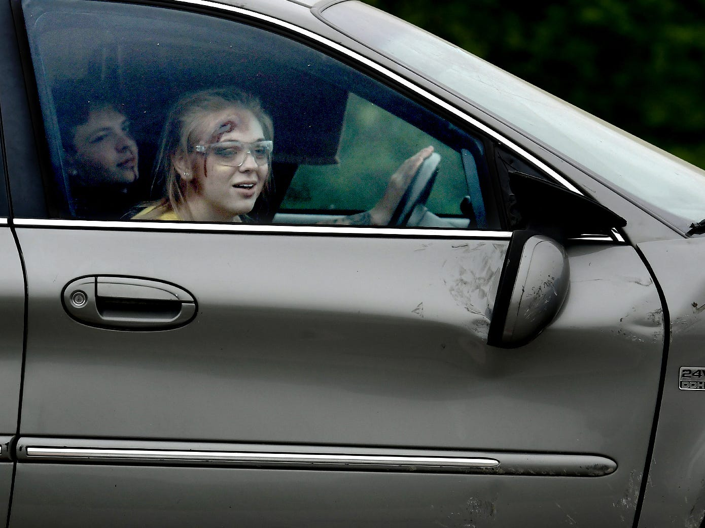 Dover High School mock accident victim, junior Victoria Brennan, peaks at senior Emma Davis during the staging at Dover Area High School Thursday, May 9, 2019. Senior Bronson Bitner sits in the driver's seat. Local fire, ambulance and police volunteered for the event which reminds high school upperclassmen to be safe during prom season. Dover's prom in Saturday, May 11. Bill Kalina photo
