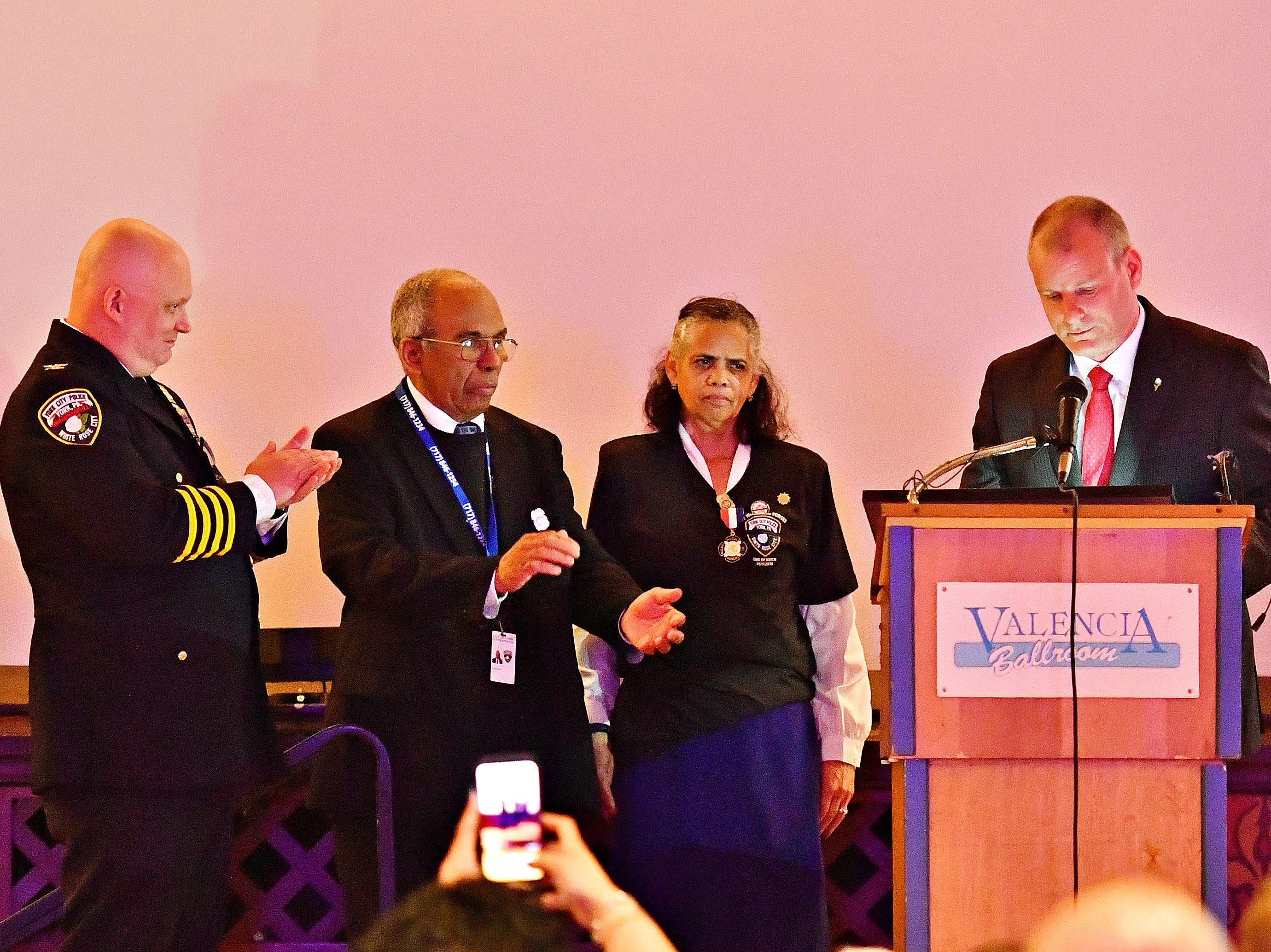 From left, York City Police Chief Troy Bankert, and Chaplains Alix and Arelis Sable look on as York City Mayor Michael Helfrich reads the official proclamation retiring badge number 187 during the York City Police Departmental Awards Ceremony at Valencia Ballroom in York City, Thursday, May 9, 2019. The badge number belonged to the Sables' son, Officer Alex Sable, 37, who died in the line of duty. Dawn J. Sagert photo