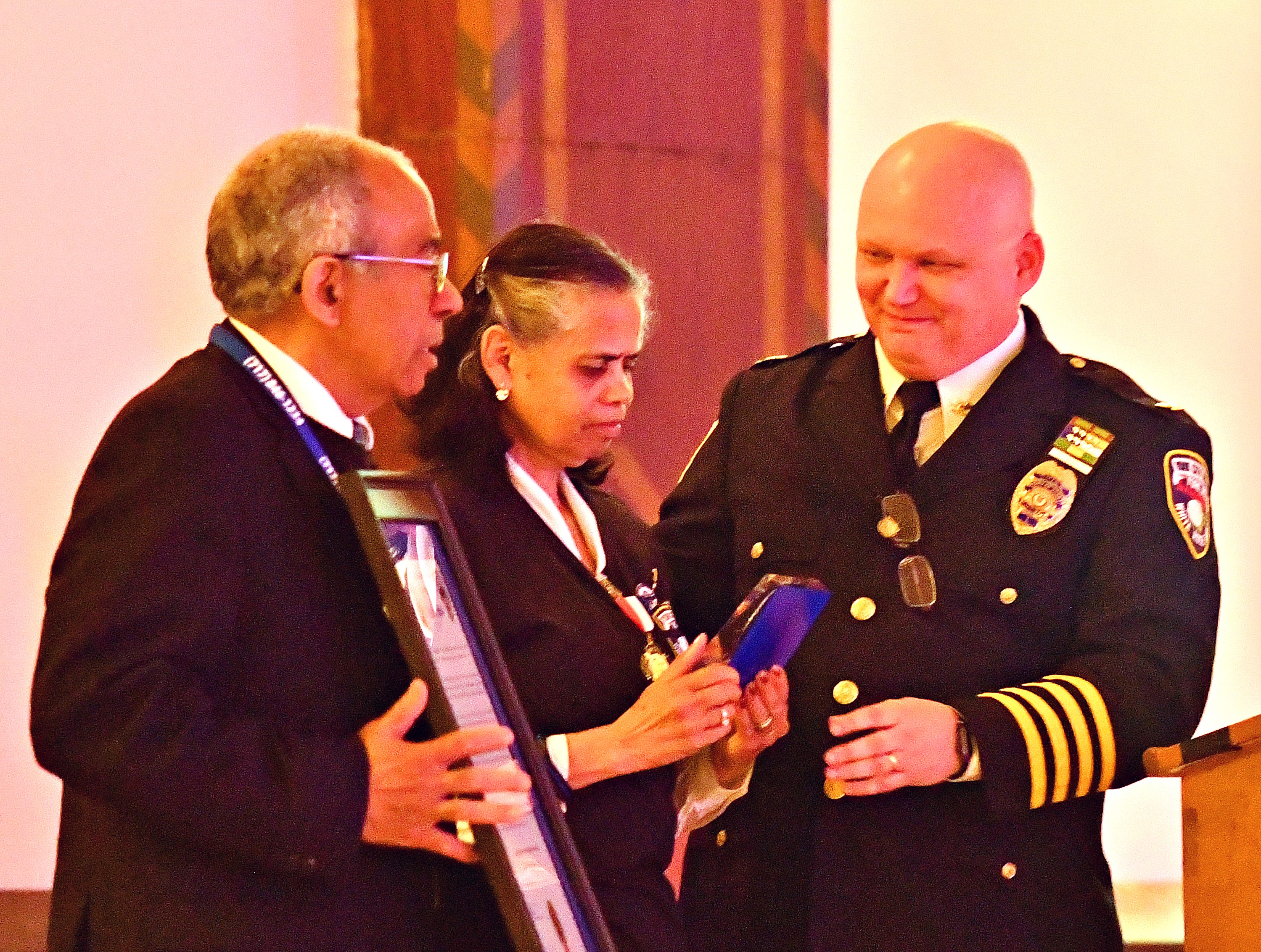 From left, York City Police Chaplains Alix and Arelis Sable are presented with badge number 187 by York City Police Chief Troy Bankert during the York City Police Departmental Awards Ceremony at Valencia Ballroom in York City, Thursday, May 9, 2019. The badge belonged to the Sables' son, Officer Alex Sable, 37, who died in the line of duty last May. Dawn J. Sagert photo