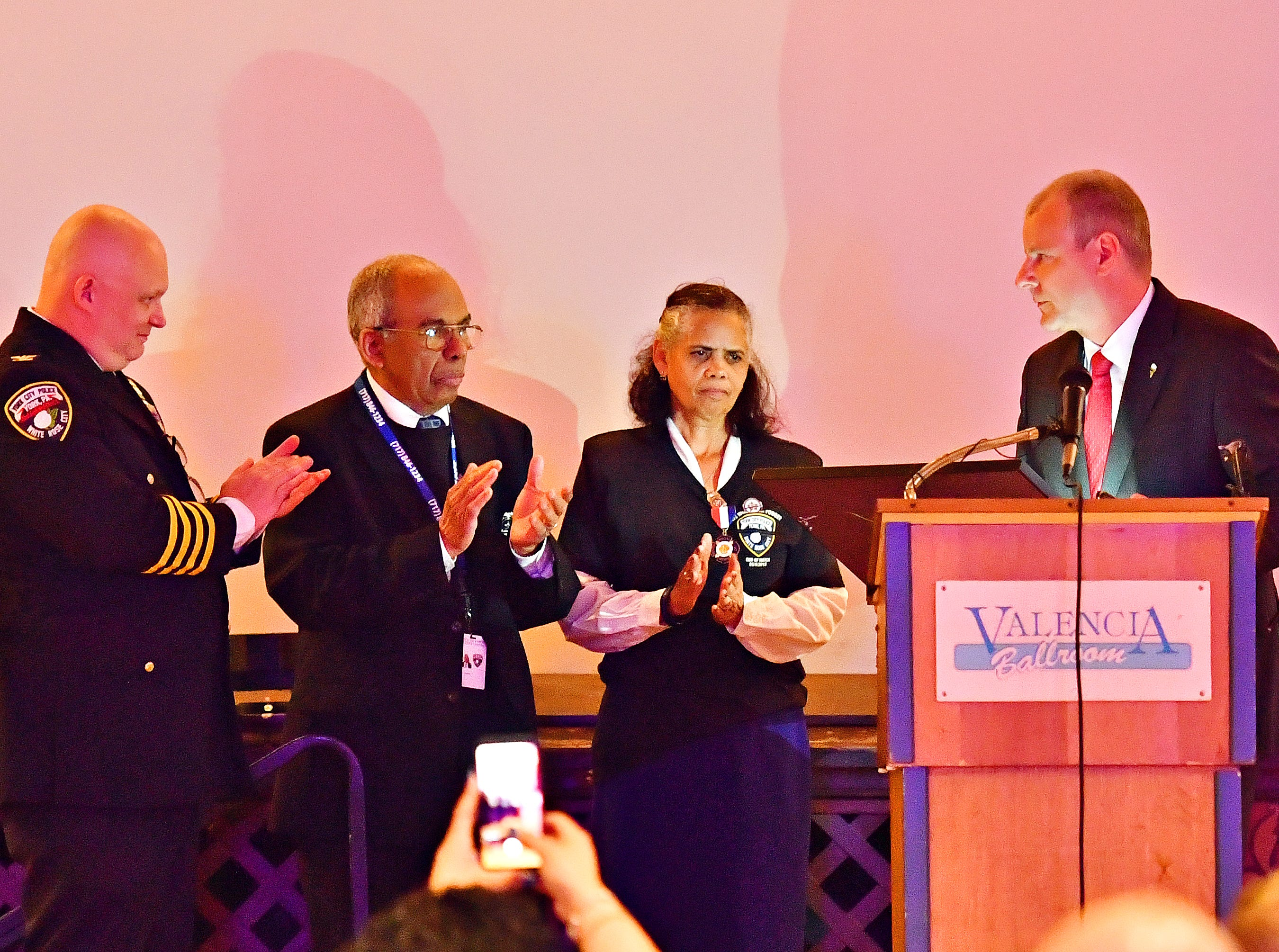 From left, York City Police Chief Troy Bankert, and Chaplains Alix and Arelis Sable look on as York City Mayor Michael Helfrich presents the official proclamation retiring badge number 187 during the York City Police Departmental Awards Ceremony at Valencia Ballroom in York City, Thursday, May 9, 2019. The badge number belonged to the Sables' son, Officer Alex Sable, 37, who died in the line of duty. Dawn J. Sagert photo