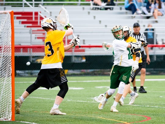 Chandler Hake (12) takes a fancy shot during the YAIAA boys lacrosse semi-final game between York Catholic and Red Lion, May 8, 2019 at Susquehannock High School. The Fighting Irish defeated the Lions 13 to 6.