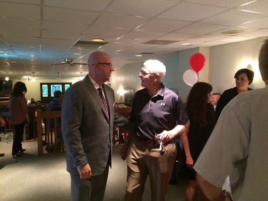 Jamie Lopeman mingle with those gathered Wednesday evening in the William G. Scott House.
