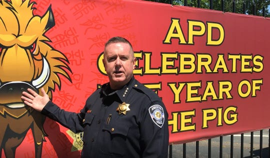 Anderson police Chief Michael Johnson explains the meaning of the banner in front of the police station celebrating the Year of the Pig.