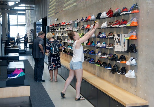 Shoppers look at shoes at the Nike Miami store on the Lincoln Road Mall in Miami Beach, Fla.