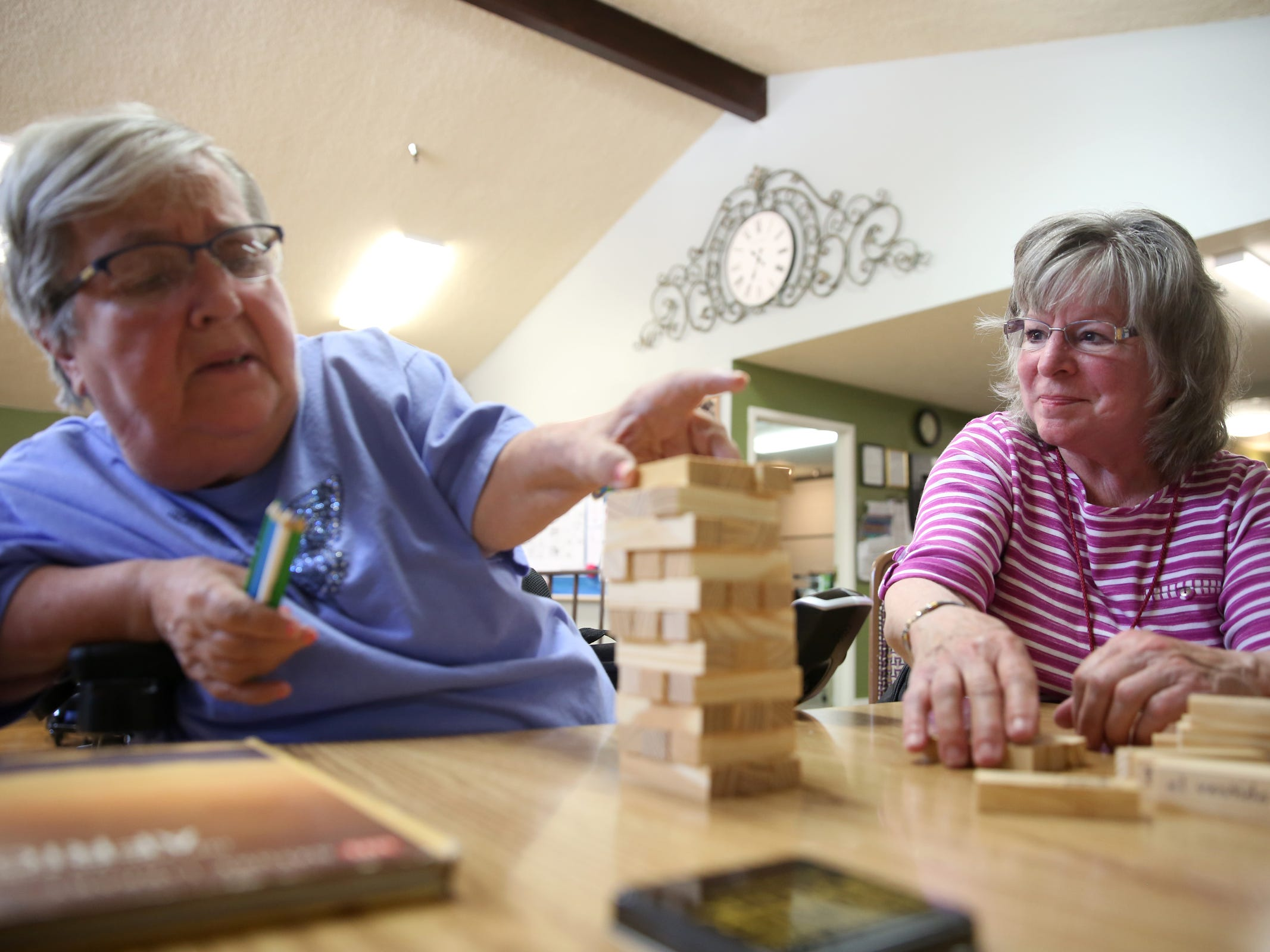 Volunteer Anita Felion, right, plays a game with Lucy Buntjer during a visit by the Friendship Brigade, a group of volunteers that focuses on spreading awareness about senior isolation and loneliness, at The Oaks at Sherwood Park in in Keizer on May 9, 2019.
