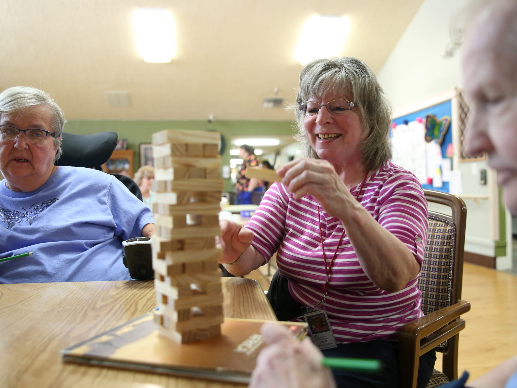 Volunteer Anita Felion, center, plays a game with Lucy Buntjer, left, and Shirley Wiltgen during a visit by the Friendship Brigade, a group of volunteers that focuses on spreading awareness about senior isolation and loneliness, at The Oaks at Sherwood Park in in Keizer on May 9, 2019.