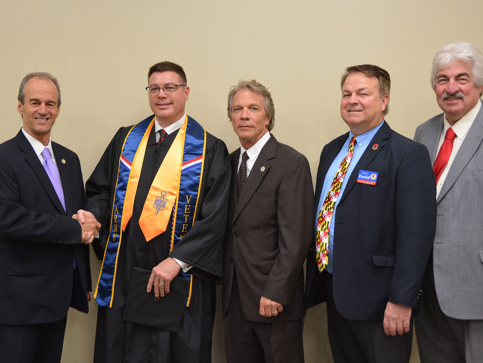 Wicomico County Executive Bob Culver congratulates Lt. Howard Drewer of the Salisbury Police Department who received his criminal justice degree at Wor-Wic Community College commencement exercises, as John Cannon, Wicomico County council president, Larry Dodd, council vice president, and Joe Holloway, council member, look on.