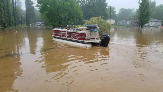 Citizens in a pontoon boat help the Bossier Parish Sheriff's Office evacuate residents in the Cannon Road area on Thursday, May 9, 2019.