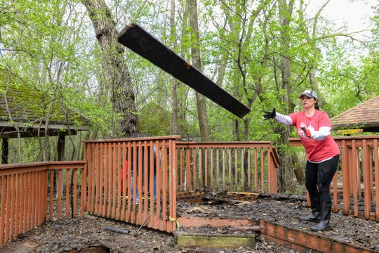Melissa Chinn tosses a rotted wooden plank into a refuse pile Thursday, May 9, at YMCA Camp Leif Ericson in Sioux Falls. Chinn, director of marketing at Keller Williams Realty, Inc., took the day to volunteer with several of her coworkers.