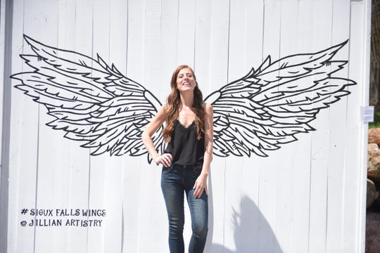 Artist Jillian Gunlicks stands in front of her Wings mural, which she finished last Thursday. Her work can be found on Instagram at @jillianartistry