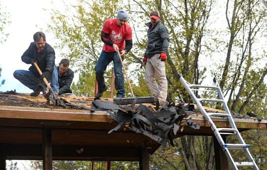 William Knowles pushes old roofing material off of a pavilion at YMCA Camp Leif Ericson on Thursday, May 9, in Sioux Falls.