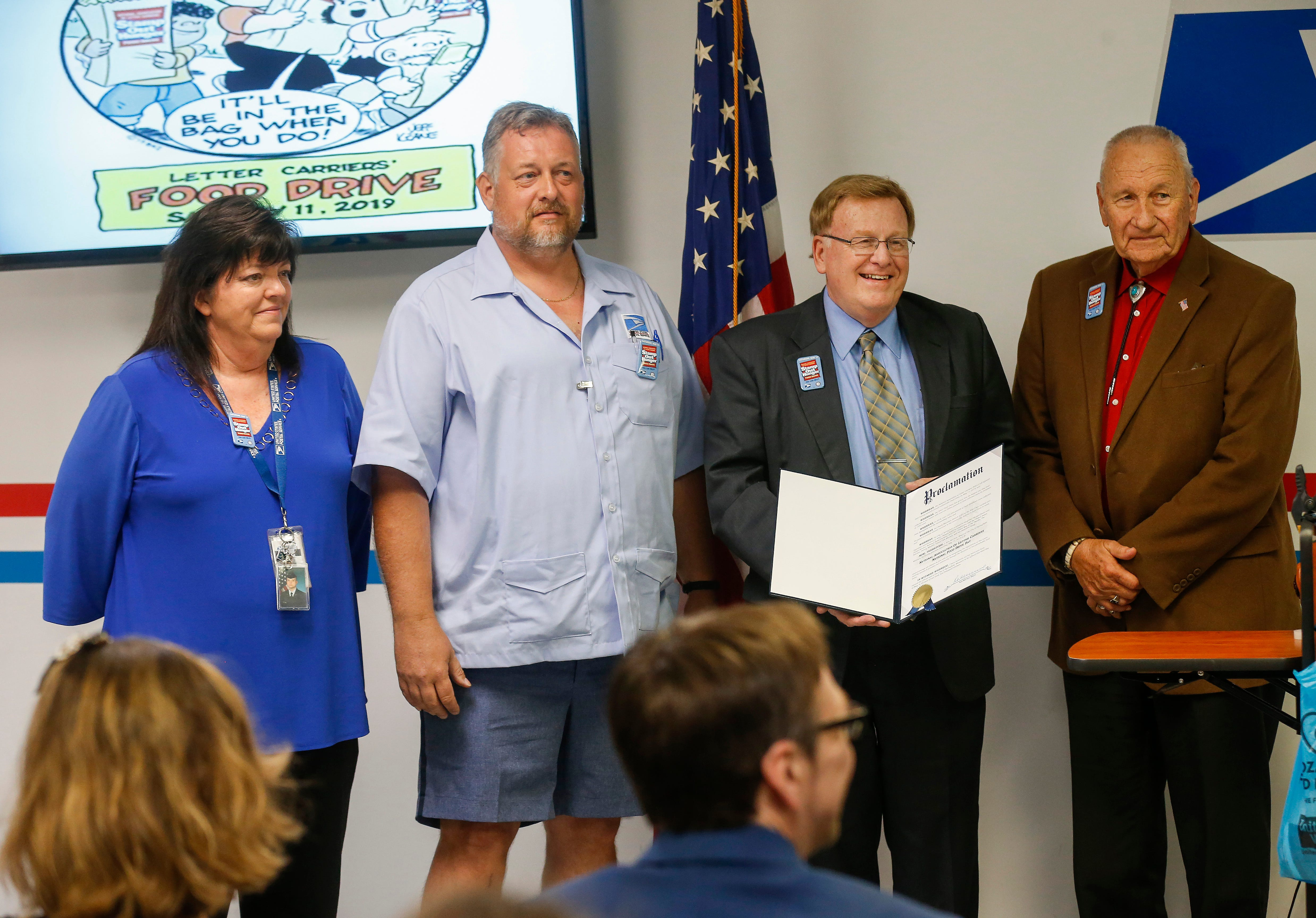 Springfield Mayor Ken McClure, center right, and Greene County Commissioner Harold Bengsch, right, present a proclamation to Terri Ryan, left, and Daryl Sexton during a press conference for the Stamp Out Hunger Food Drive on Thursday, May 9, 2019.