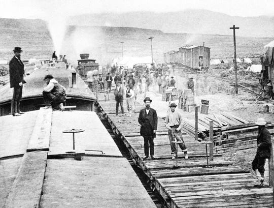 """FILE - In this April 28, 1869, file photo, workers laying tracks for Central Pacific Railroad pause for a moment at camp """"Victory,"""" a few miles from Promontory, Utah. The May 10, 1869, completion of the Transcontinental Railroad was a pivotal moment in the United States, ushering in a period of progress and expansion nationwide. The presidents of the Union Pacific and Central Pacific railroads met in remote Promontory, Utah, to mark the occasion, driving a last ceremonial spike to connect their rail lines. (AP Photo, File)"""