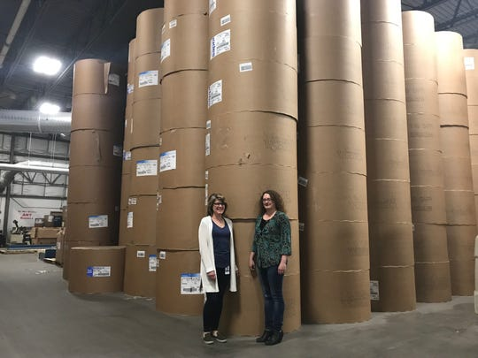"""Kathy Ladwig and April Kemnitz worked on the project and coordinated with the publisher to print """"Diary of an Awesome Friendly Kid."""" They are standing next to rolls of paper. It took 49 trucks to deliver all of the paper needed for the project."""