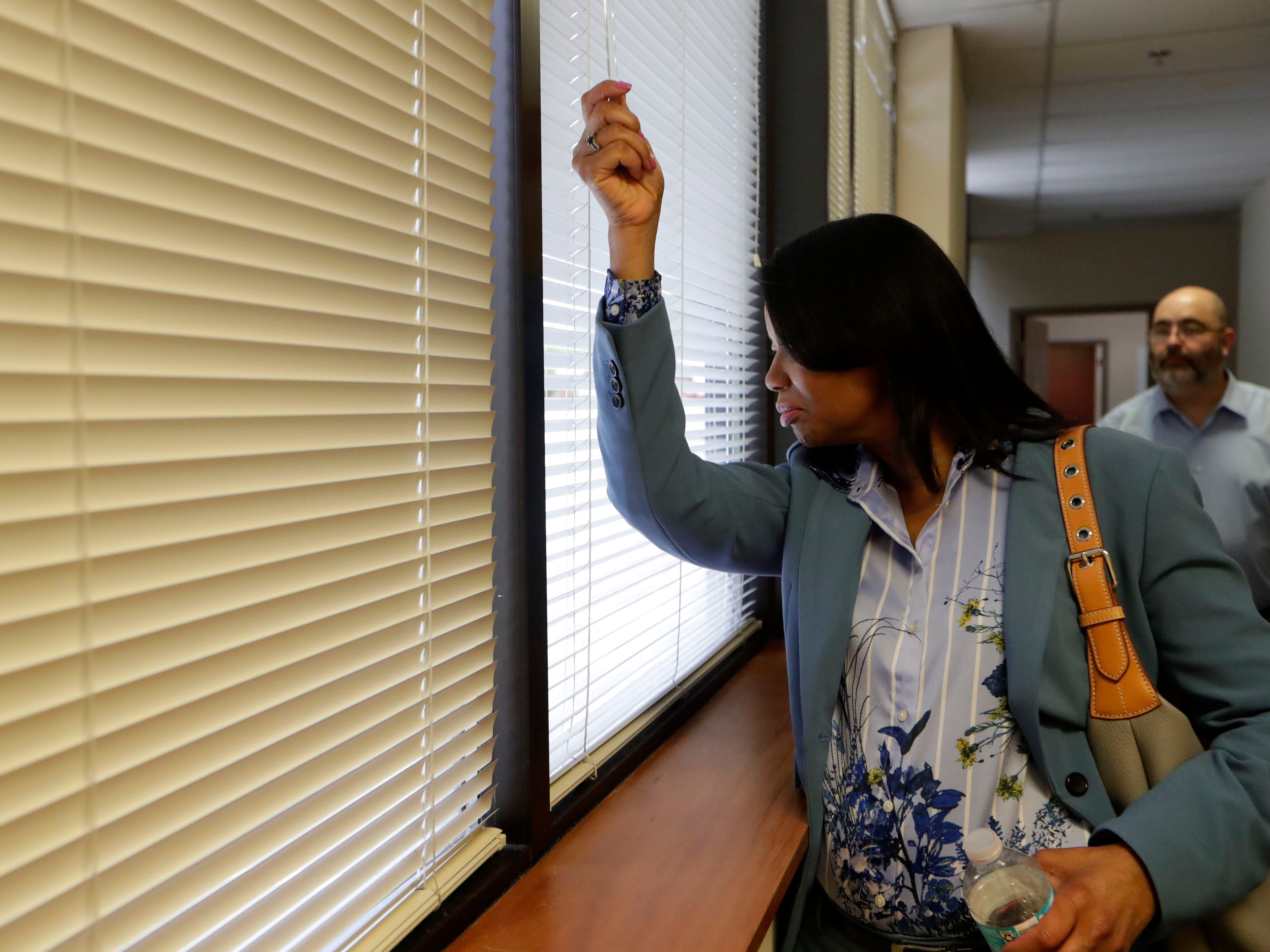 Cassandra Jackson, city attorney, peers through the blinds at a parking lot while touring the Northwood Centre Wednesday, May 8, 2019.