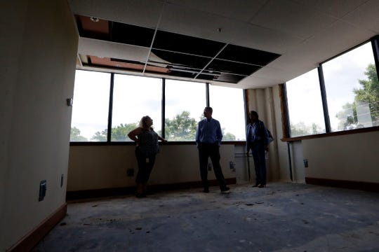 Judy Donahue, who works with the city's real estate department, left, Wayne Tedder, assistant city manager, and Cassandra Jackson, city attorney, tour vacant office spaces inside the Northwood Centre Wednesday, May 8, 2019.