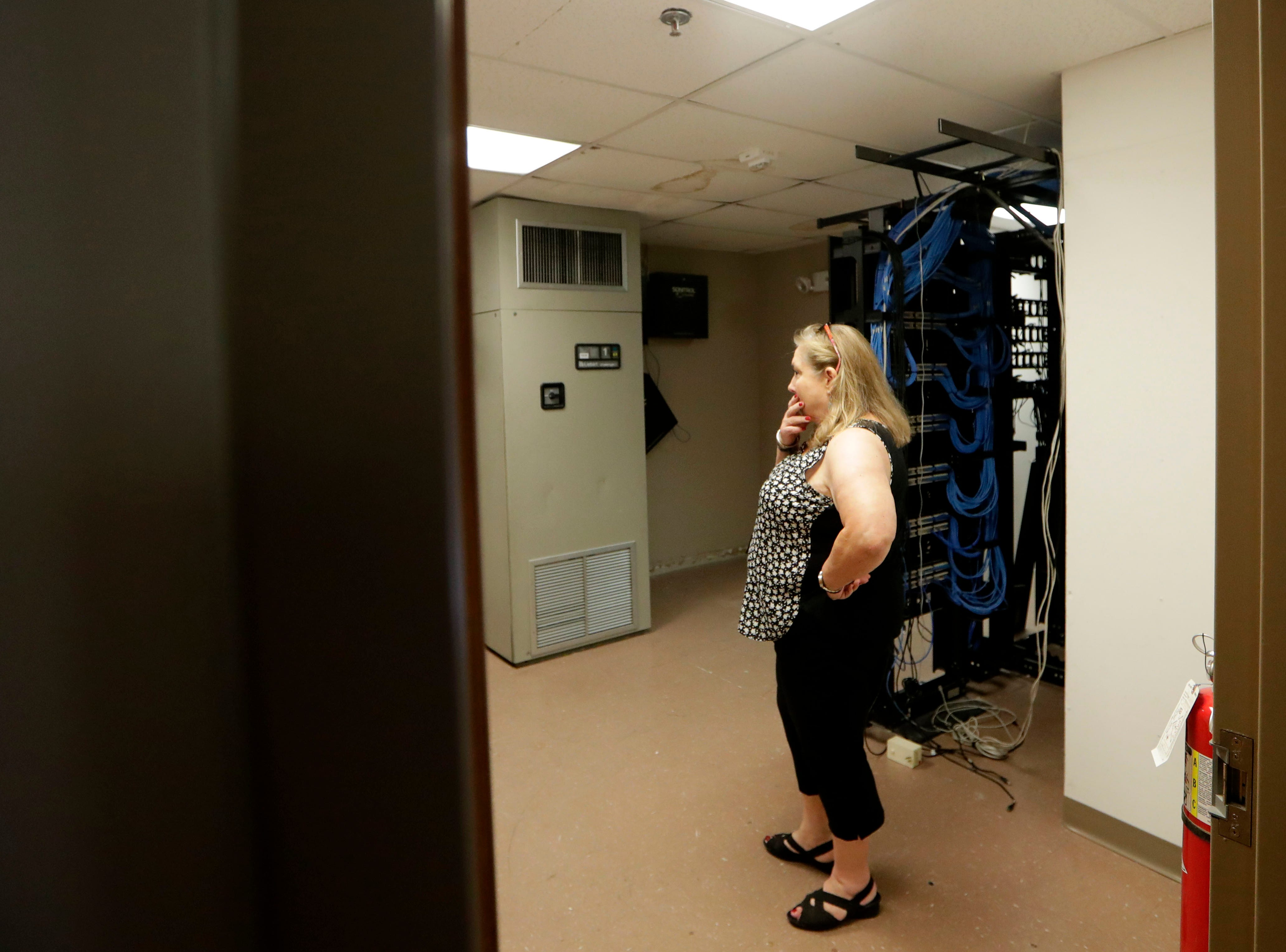 Judy Donahue, who works with the city's real estate department, looks at a room full of wires and electrical equipment as she tours office space at the Northwood Centre Wednesday, May 8, 2019.