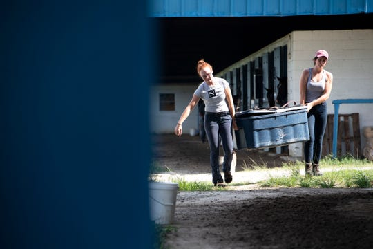"Megan Johnston (left), exercise rider, and Jamie Riordan, assistant trainer, move items out of a Payson Park horse barn Thursday, May 9, 2019, at the training facility in Indiantown. Typically, young horses come to train on the property from November to May, and this year's group included Country House, Code of Honor and Tacitus, the top three finishers of the 145th Kentucky Derby. ""They both had big personalities,"" Riordan said, who helped train Country House and Tacitus. ""(Country House) doesn't focus a ton, but he is one of the most athletic horses I've ever met in my life. Tacitus came in looking like a donkey. As we developed him ... he's the perfect specimen now. He really grew into his body."""