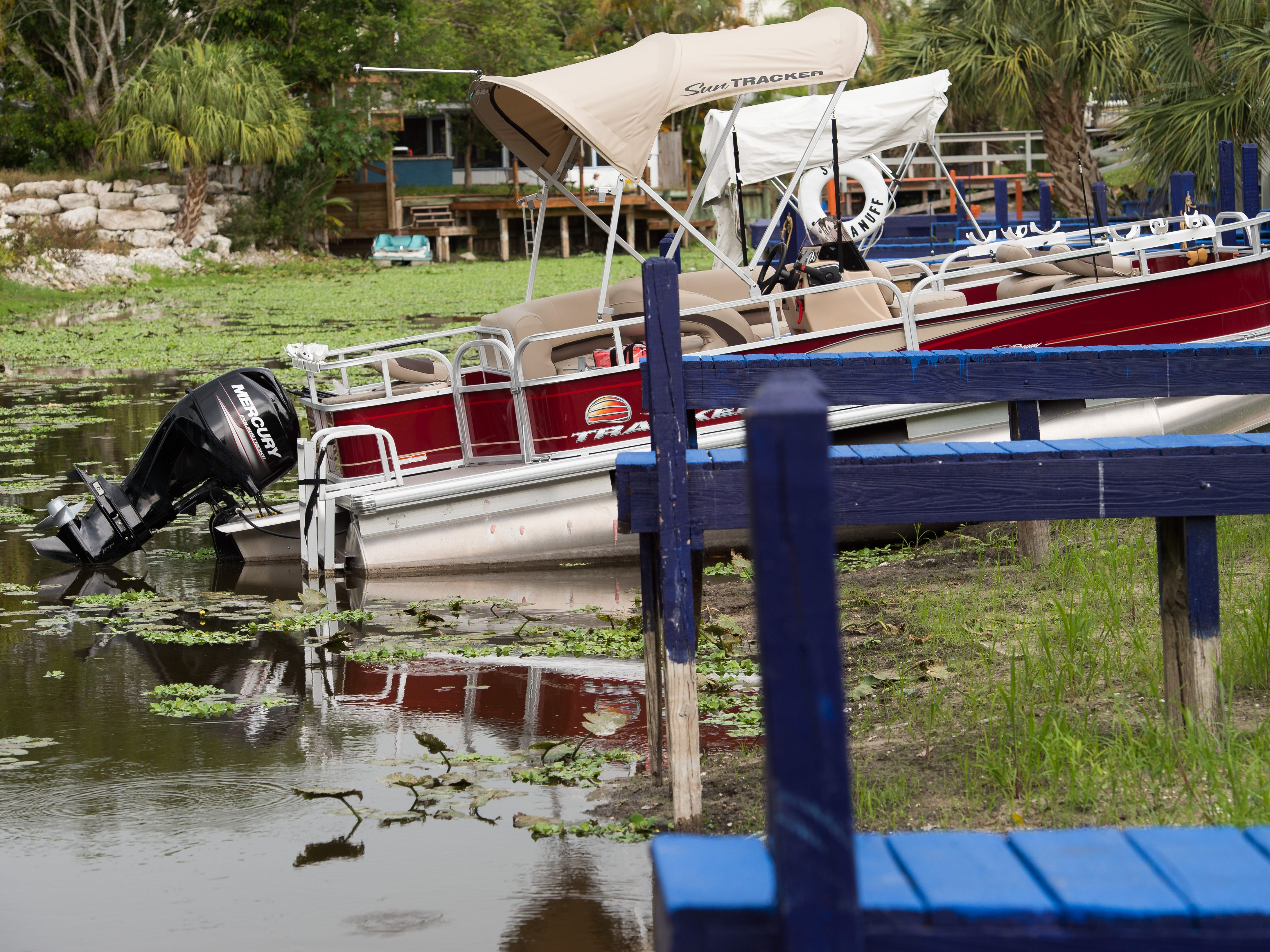 """A boat sits in shallow water at a canal dock at J & S Fish Camp near the border of Martin and Okeechobee counties Tuesday, May 7, 2019, off Lake Okeechobee. """"It's killing our business,"""" said business owner Terrie Birkett. """"I've got more cancellations right now than I've ever had because they can't go fishing."""""""