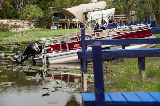 "A boat sits in shallow water at a canal dock at J & S Fish Camp near the border of Martin and Okeechobee counties Tuesday, May 7, 2019, off Lake Okeechobee. ""It's killing our business,"" said business owner Terrie Birkett. ""I've got more cancellations right now than I've ever had because they can't go fishing."""