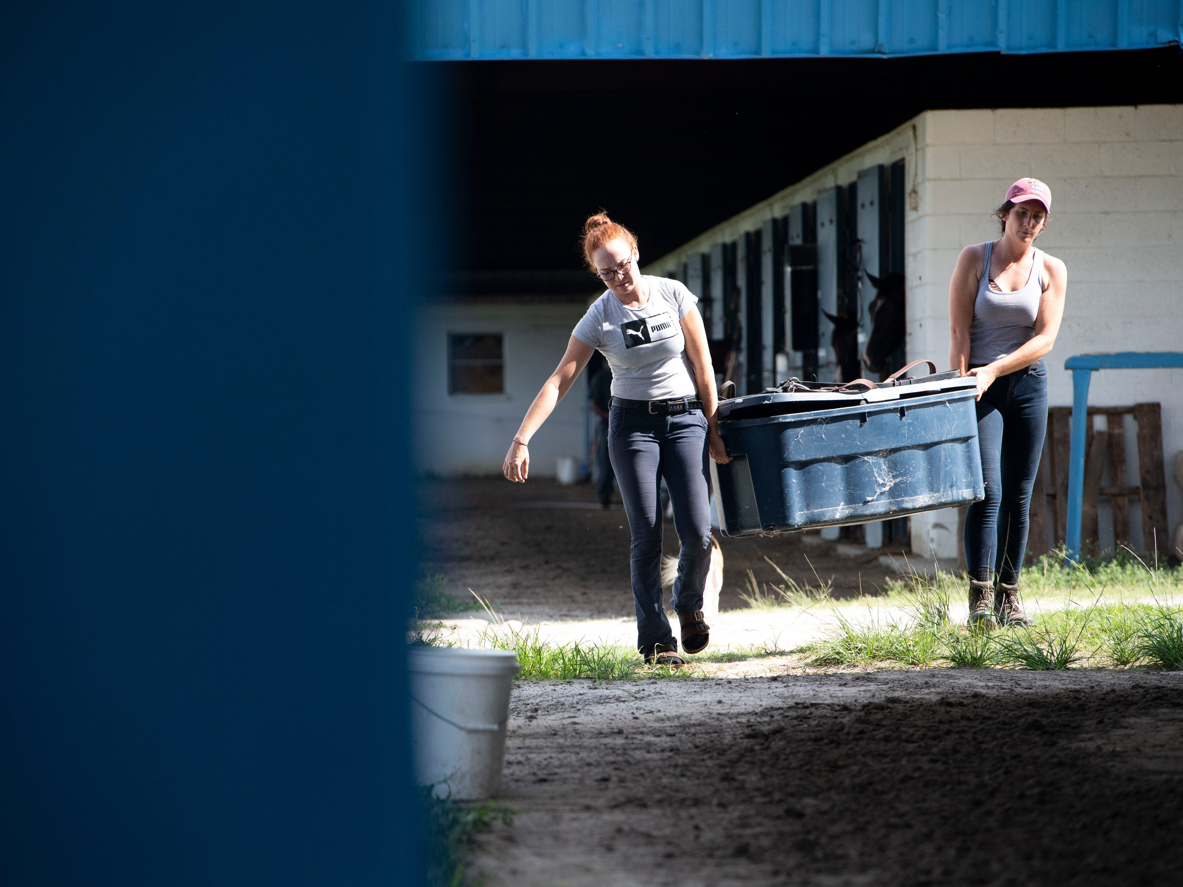 "Megan Johnston (left), exercise rider, and Jamie Riordan, assistant trainer, move items out of a Payson Park horse barn Thursday, May 9, 2019, at the training facility in Indiantown. Typically, young horses come to train on the property from November to May, and this year's group included Country House, Code of Honor and Tacitus, the top three finishers of the 145th Kentucky Derby. ""They both had big personalities,"" Riordan said, who helped train Country House and Tacitus. ""(Country House) doesn't focus a ton, but he is one of the most athletic horses I've ever met in my life. Tacitus came in looking like a donkey. As we developed him... he's the perfect specimen now. He really grew into his body."""