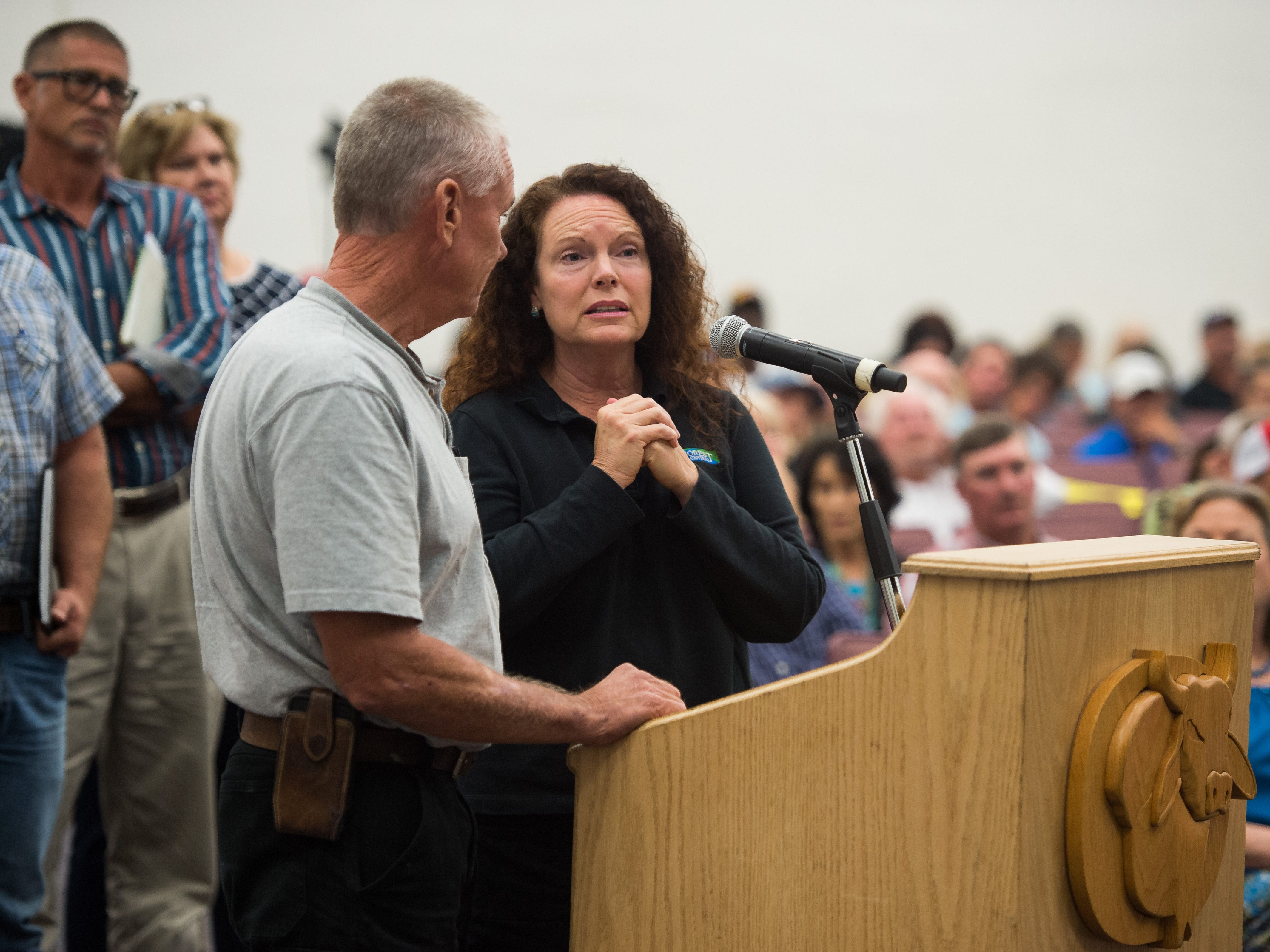 Okeechobee resident Tracy Campbell, who works in Stuart as director of sales and marketing for River Forest Yachting Centers, speaks during a joint commission meeting at Okeechobee High School on Tuesday, May 7, 2019, while her husband, John Helfrich, manager of River Forest Yachting Centers in LaBelle, stands beside her. Campbell and Helfrich spoke about how every aspect of their life is tied to Lake Okeechobee, and how the lowering water level has negatively affected business. County commissioners from Martin, Palm Beach, Glades, Hendry and Okeechobee attended the meeting, where stakeholders voiced their concerns following statements from the Army Corps of Engineers and Rep. Brian Mast's office.