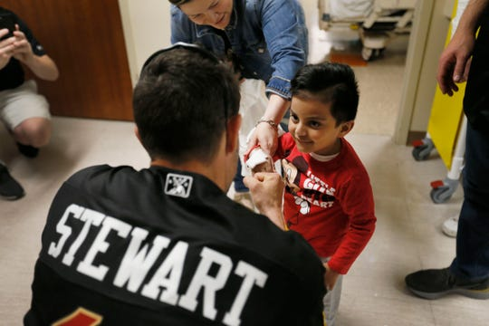 Alejandro Almeralla gets a jersey from El Paso Chihuahuas catcher Chris Stewart during the team's visit to Providence Children's Hospital on Thursday, May 9, 2019. Chihuahuas players Dietrich Enns, Logan Allen, Chris Stewart and Mathew Batten went room to room visiting with patients.